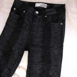 Oanvända svarta jeans med ormskinn tryck. Storlek 34. Lite tajtare vid midjan o lösare från knäna och neråt. Säljer pga lite för små i midjan.