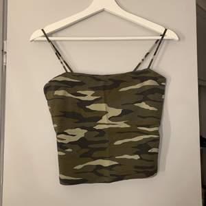 Ett militärmönstrat linne från Gina Tricot i storlek M men passar XS och S också. Väldigt bra skick då det knappt är använt🤍