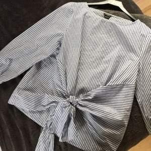 NYTT PRIS - Jättefin randig blus som du själv knyter i midjan. Köpt förra sommaren på Lindex. Använd några gånger men i gott skick. Frakt tillkommer, alt möts vi upp i Göteborgsområdet.