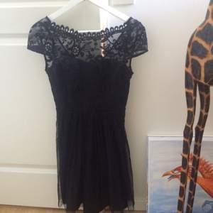 Svart spetskläning från vila som är perfekt till fest eller konserter. Kom aldrig till användning i min garderod då jag har ett flertal liknande klänningar. Superfim rygg med knäppning!