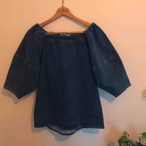 """Skjorta med puffärmar, i jeansmaterial och med """"fyrkantsurringning"""". Aldrig använd så i nyskick! Skulle säga att den passar fler storlekar än M. Skriv för mer bilder/info. Kan mötas upp i Gbg/köparen står för frakten."""