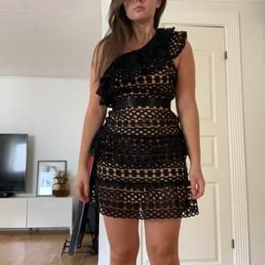 Svart One shoulder klänning från Vila, inköpt från Nelly. Storlek 34, men passar också mig som bär 36. Klänningen har som spets-volanger