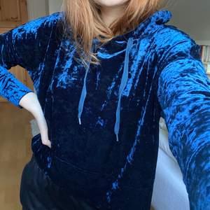 Lite croppad blå hoodie i materialet krossad sammet. Passar bra på mig som är 174 cm lång. Mycket bra skick, som ny. 💜FRAKT INGÅR I PRISET💜