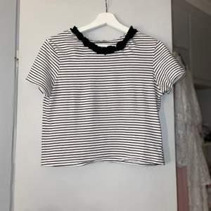 """En randig t-shirt som är lite kortare i modellen! Den har som en liten """"volang"""" runt halsen. Jätteskön & fin som passar till det mesta! Storlek S men kan passa allt från XS-M beroende på hur man vill att den ska sitta🤍"""