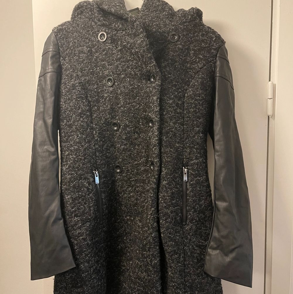 En grå/svart kappa med en stor liva och läderimitations ärmar. Jackor.