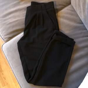 Svarta kostymbyxor med resår i midjan, 2 fickor fram och 2 fake fickor baktill. Har tyvärr blivit för små
