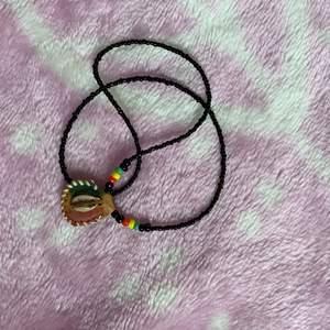 Halsband som är lite rastaliknande med en snäcka. 60 inkl frakt💟