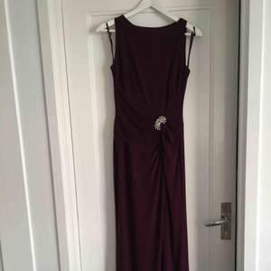 Mycket fin lila långklänning från Ralph Lauren, endast använd en gång. Vacker dekorativt smycke på klänningen och slits nertill. Passar storlek 36/38.   Ord.pris 2295 kr säljs nu för 1300 kr