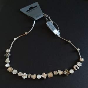 Halsband från Pilgrim helt oanvänt! Dekorerat med blommor, gnistrande stenar, hästhov etc.