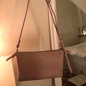 """Liten rosa väska med justerbart band. 5 stora """"avdelningar"""" inuti samt flera småfack. Som ny förutom en liten fläck inuti ett av facken.💕✨"""