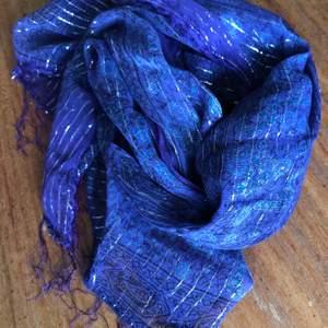 Lila sjal med silvertrådar. Kan hämtas i Malmö, är lite osäker på exakt fraktkostnad.