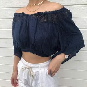 somrig mörkblå/marinblå crop-top i gott skick. kan bäras som off - shoulder eller vanlig blus & kan knytas fram.