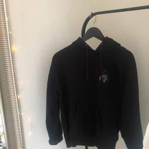 svart hoodie med ett märke, vet inte var den är ifrån