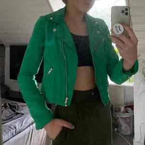 En grön jacka av mocka med silvriga detaljer. Sjukt snygg modell i storlek 36. Något tajt men i övrigt sitter den som en smäck.