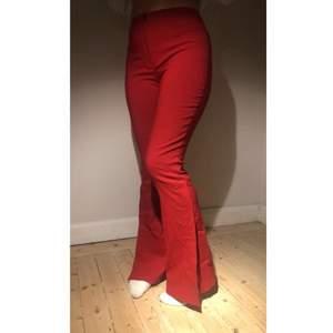 Röda utsvängda byxor med slits i storlek 42. Små i storleken, mer som ca 36. Stretchigt tyg, köpta secondhand och säljes pga att de inte har blivit använda tillräckligt. Liten prick på ena benet.