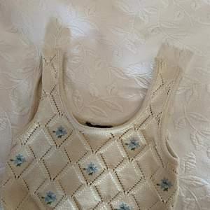 Stickat linne i naturvit färg med små blommor.