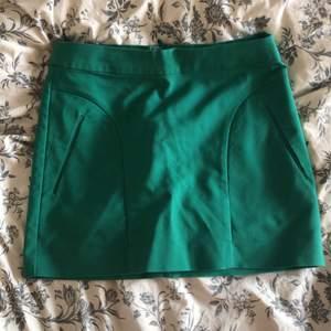 Säljer en fin grön kjol som tyvärr är för liten. Kjolen är kort och har fake fickor på framsidan. Dragkedja bak på kjolen. Sömmarna vid fake fickorna har gått upp lite men inget som syns. Köparen står för frakten eller kan jag mötas upp i Lund!