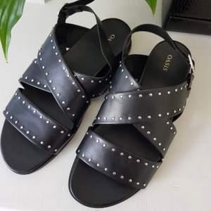 Svarta sandaler med nitar från Oasis! Tjocka remmar så ger en gladiator vibe. Väldigt bekväma och mjukt imitation läder. Reglerbara band baktill. ALDRIG använda så i utmärkt skick!