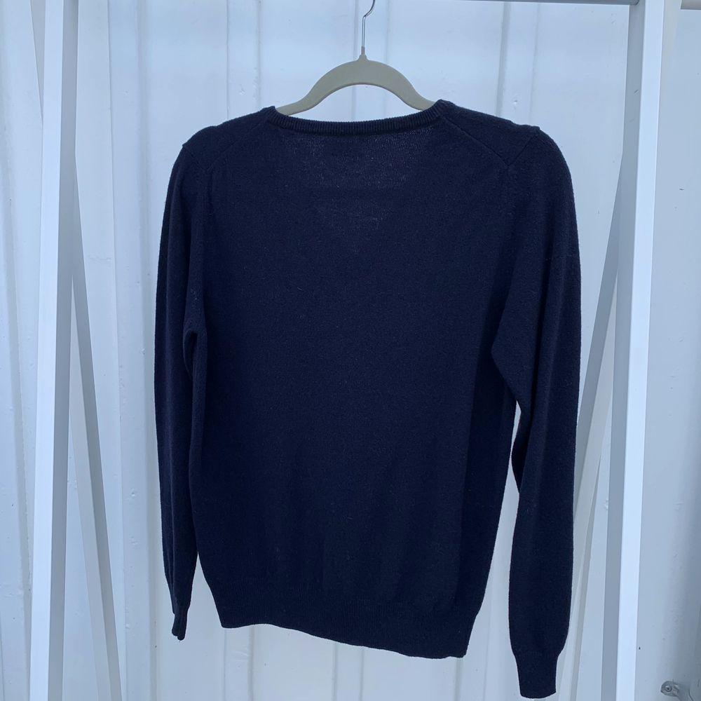 En v-ringad tunnstickad tröja ifrån GANT i en marinblå färg och med ett vitt broderat märke på vänster bröst. Endast använd en gång och är i nyskick. (Material: 80% ull och 20% polyamid). Tröjor & Koftor.