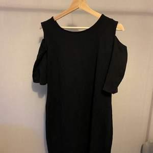 En ganska tight svart klänning med detaljer på axlarna!