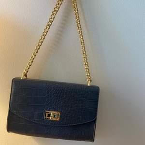 En super snygg blå väska från NAKD med gulddetaljer. Väskan har bara använts en gång och axelbandet är fortfarande oöppnat. Det ser ut som att det är fläckar men jag fick väska så ( ni kan se på bild 2) inget man märker💞