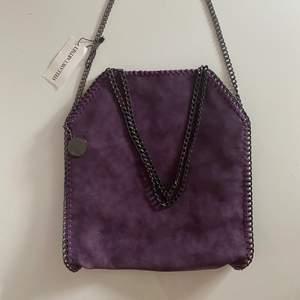 Fake Stella McCartney väska i lila färg. Alldrig använd med lappen fortfarande kvar. Inga defekter helt ny.