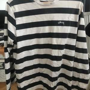"""longsleeve stussy tröja. storlek S, passar mig oversized som är en XS. Fint skick. Svarta färgen """"blekts"""" lite vid tvätt, ingenting som man tänker på. Köpt för 900. PRIS: 500 (pris kan diskuteras)"""