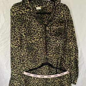 """Pyjamas set från hm i leopard print. Skjorttröja med leopard mönster med texten """"lovestories"""" broderat på fickan och pyjamasbyxor me leopardmönster och ett resår som det står love runt. Endast testad och säljs för att den är för liten."""
