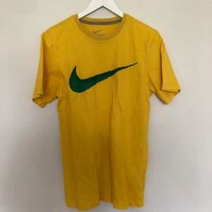 Vintage Nike T-Shirt i storlek Small. Den har en fin gul färg som är perfekt inför sommaren. Swoosh är printad och är i bra skick. Vintage skick med inga defekter.