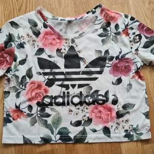 Blommig croppad t-shirts från Adidas. Använd men i gott skick. Storlek XS men passar XS-S-M. 100kr +frakt