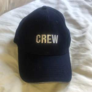 """Marinblå keps med vit text """"CREW"""". Oanvänd."""