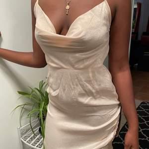 Säljer denna nude satin klänning med en split vid sidan om, justerbara axelband. Aldrig använd bara testad, dragkedja vid sidan & öppen rygg