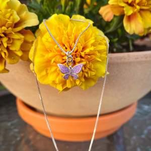 Ett halsband med en lila glittrig fjäril på. Kedjan är 35 cm lång  //Samfraktar gärna om du köper mer än en sak 😊