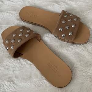 """Säljer sandaler i beige mocka med silvriga """"nitar"""",  i 38. Aldrig använt dessa utomhus, helt nya. De enda är att skinnet på ena skon längst fram där stor tån ska vara har vikt sig pyttelite se bild 3, men inget som syns när du har foten i!! Ny pris 449 kr säljer för 150 kr. Köparen står för frakten!"""
