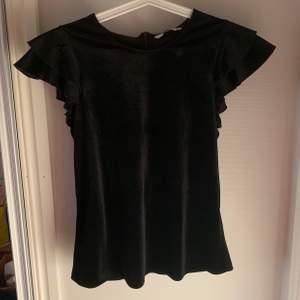 Svartglittrig T-shirt med volangärmar. Storlek 36