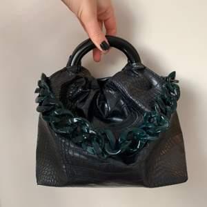 Riktigt cool handväska från NA-KD i orm mönster med en grön kedja som detalj! Knappt använd och i ett väldigt bra skick!