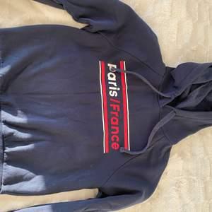 En vanlig blå hoodie med text på. Nästan aldrig använt. Är mjuk och i skönt material!
