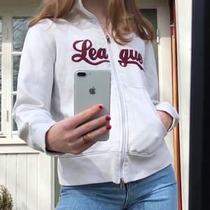 """Zipup hoodie i gräddvit färg som det står """"league"""" på. Jättebra skick och passar till mycket. Den är köpt second hand! ❤️ Frakten är 66 kr"""