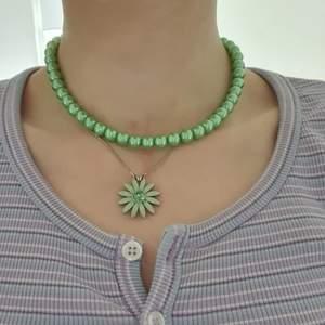 Ett egengjort grönt pärlhalsband med elastiskt band🍀OBS halsbandet med blomman är inte till salu. DM vid frågor💚 Står ej för frakt. KOLLA IN PROFIL FÖR FLER SAKER😊