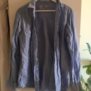 Ljusblå linneskjorta. Herrskjorta i storlek L men har fin passform om man gillar oversized. Sorry att den e ostruken men ni fattar stuket...