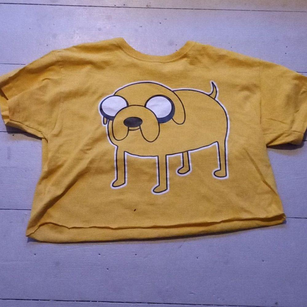 T-shirt från Fruit of the loom med Jake från Äventyrsdags som jag klippt till en magtröja. Knappt använd. Står inuti att det är storlek 140 men passar bra på en liten XS. Lite sprickor i trycket (se bild) men inga andra skador/fläckar. BETALNINGSMETOD: SWISH (PÄLSDJUR I HEMMET). T-shirts.
