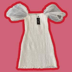 Vit klänning som har original lappen kvar och är endast testad ☁️ Väldigt stretchig och skulle därför passa de flesta storlekarna, jag har vanligtvis M/L och den passar bra på mig ☺️ Säljer då den aldrig kom till användning