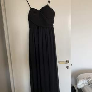 Superfin svart långklänning, oanvänd då den är för liten. Inbyggd bh, justerbara axelband, dragkedja i sidan och silikonrand vid brösten så den sitter uppe. Storlek 10 eller M