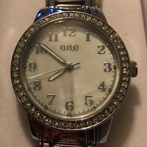 Jätte fin klocka från one. Sparsamt använd, silverfärgad med pärlemor + boxen den låg i.