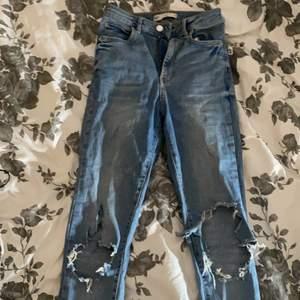 Ljusblåa skinny jeans med hål i knäna. Kan skicka bild på hur som sitter om så önskas. Storlek 36 men kan även passa 34 och 38. Högmidjade med stretchigt material. Säljs då de inte används längre