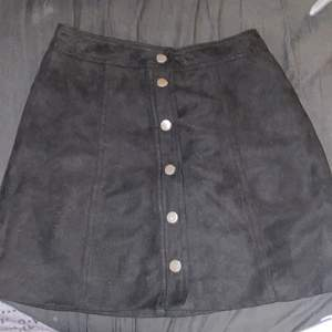 En svart h&m kjol i Sämskskinn med metall framknappar, den sitter jätte fint på och sitter vid knäna. Ny och aldrig använd då det inte är min stil längre men annars jätte gullig😊🖤!!