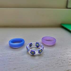 Fina resin ringar. Två lila ringar och en med lila blommor. Alla tre ringar är samma storlek, 18mm inre diameter. Kostar 30kr för alla tre ringar + frakt.