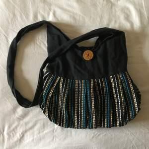 väska i bohemisk stil med vacker decor. stänges med dragkedja eller med en stor trä knapp. rymlig med en lite hårdare platta i botten.