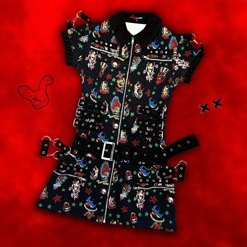 """""""𝑼𝒏𝒕𝒂𝒎𝒆𝒅 𝒂𝒏𝒅 𝒖𝒏𝒍𝒆𝒂𝒔𝒉𝒆𝒅."""" Hey, you! Live out your wildest rockabilly dreamz i 'Rocka Bondage Dress' från Hell Bunny🐰🔥⛓ Maxad med öljetter, kedjor, D-ringar, blixtlås, äkta fickor och avtagbara remmar fram/bak 🖤  Med snyggt 50's inspirerat rockabilly motiv 👌🏻 Storlek S men kan göras tajtare eller lösare med sidospännena/bältet (midjemått 64-80cm och totallängd 76cm); supersnygg passform är lovad oavsett!! 📏✨ Certified deadstock! ⚰️ Inköpt 2011 för ca 860kr. Jag är 160cm. Frakt tillkommer på 66kr 💌. Klänningar."""