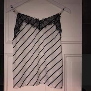 Ett randigt linne som är svart och vitt och har svart spets längst upp på linnet. Det finns även justerbara band. Storlek xs men passar s.
